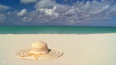 Elegant straw sun hat on white sandy beach & aqua blue sea — Stock Video
