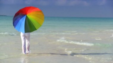 Serene young female with a parasol of rainbow colors on a beautiful white sandy beach — Stock Video