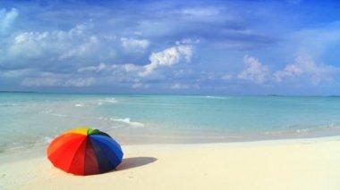 Gökkuşağı şemsiye arkasındaki su yeşil su ile güzel beyaz kumlu plaj üzerinde — Stok video