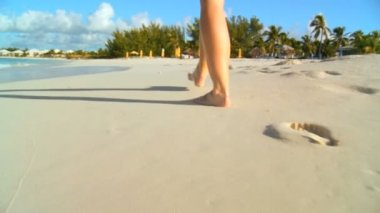 Young caucasian girl leaving footprints in the white sand of a tropical beach — Stock Video