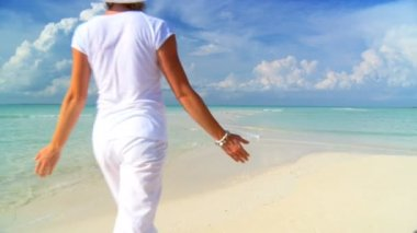 Elegant young female walking on a beautiful white sandy beach looking at aquamarine waters — Stock Video