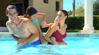 Attractive young caucasian family enjoying leisure time together in their luxury swimming pool — Stock Video