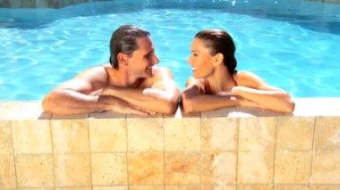 Молодая пара кавказской, наслаждаясь свободное время вместе в их бассейне — Стоковое видео