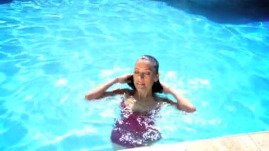 Attractive young caucasian female enjoying leisure time in her swimming pool — Stock Video