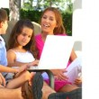 Attractive young caucasian family using a laptop outdoors to make future plans - Stock Photo