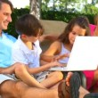 Royalty-Free Stock Vektorgrafik: Attractive young caucasian family using a laptop outdoors to make future plans
