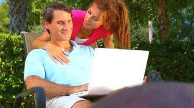 Attractive young heterosexual couple using a laptop outdoors to make future plans — Stock Video