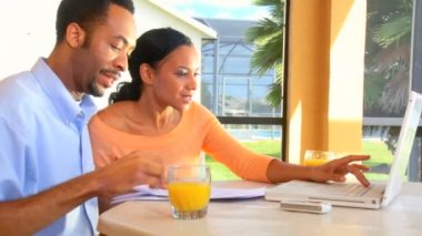 Attractive young african american couple using a laptop to make future plans — Stock Video