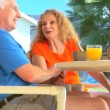 Stock Video: Contented retired couple enjoying healthy outdoor breakfast lifestyle
