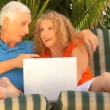 Attractive senior couple using a laptop to make future plans — Stock Video