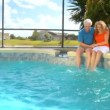 Happy retired couple enjoying a healthy outdoor lifestyle by their swimming pool — Stock Video