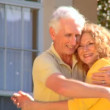 Attractive senior couple excited about their retirement real estate property move - Stock Photo