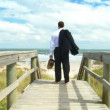 Smart young businessman taking time out from the office on the beach — Stock Video