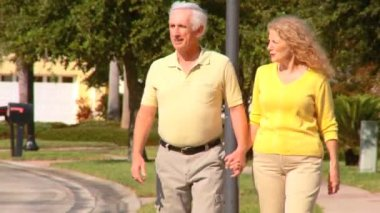 Contented retired couple enjoying a healthy outdoor lifestyle out walking — Stock Video
