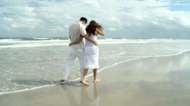 Aantrekkelijke jonge kaukasische sweethearts lopen samen op het strand — Stockvideo
