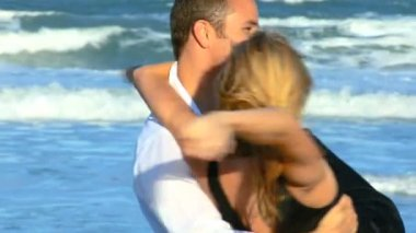 Two young in love enjoying time on the beach early morning after a social night out — Stock Video