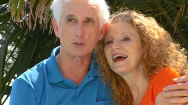 Atractiva pareja senior disfrutando juntos de ocio al aire libre junto a una piscina — Vídeo de stock