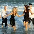 Four attractive young friends having crazy fun in the ocean early morning after a social night out — Stock Video #21040125
