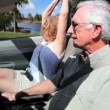 Contented retired couple enjoying driving in the sunshine in their open top car - Stock Photo