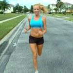 Beautiful blonde female enjoying jogging along suburban roads in the sunshine — Stock Video