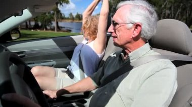 Contented retired couple enjoying driving in the sunshine in their open top car — Stock Video