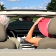 Contented retired couple enjoying driving home in the sunshine in their open top car — Stock Video #21050339