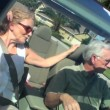 Contented retired couple enjoying driving home in the sunshine in their open top car — Stock Video