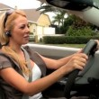 Successful young businesswoman using hands-free communication technology while driving her luxury car — Stock Video