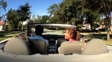 Attractive caucasian family enjoying driving home in the sunshine in their open top car — Video Stock