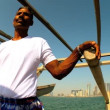 Middle-eastern fisherman steering his traditional wooden dhow — Stock Video