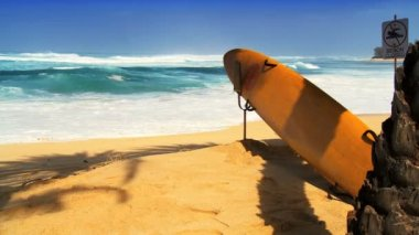 Lifeguard rescue surf board on golden sand beach  with aqua sea background