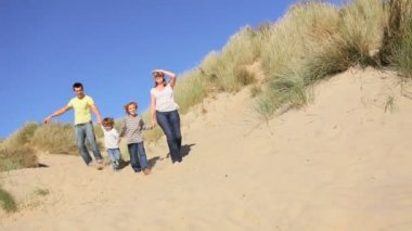 Attractive young caucasian family enjoying vacation time together on coastal sand dunes
