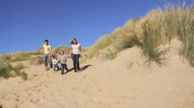 Attractive healthy young caucasian family having fun together on coastal sand dunes