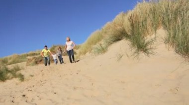Attractive healthy young caucasian family enjoying leisure time together on coastal sand dunes