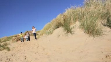 Attractive young caucasian family enjoying leisure time together on coastal sand dunes