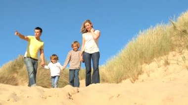 Attractive young caucasian family enjoying leisure time together on coastal sand dunes  filmed at 60FPS