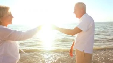 Attractive romantic senior couple dancing on the beach & enjoying a carefree lifestyle