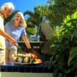 Seniors Grilling Barbeque Food - Foto Stock