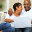 Young Ethnic Couple Using Laptop at Home - ストック写真