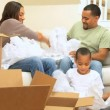 Happy Family Unpacking From House Move - Stock Photo