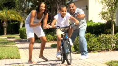 Cute young african-american boy being encouraged by his parents as he learns to ride his bicycle