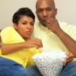Ethnic Couple Watching Scary Movie with Popcorn - Stock Photo