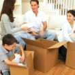 Young Caucasian Family Unpacking in New Home - Stock Photo