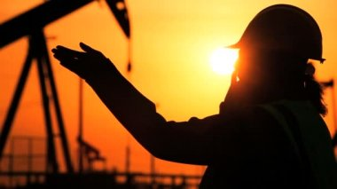 Silhouette of female engineer with clipboard using a cell phone overseeing the site of crude oil production at sunset — Stock Video