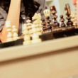 Young Female Playing Chess With a Friend - Stock Photo