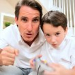 Father &amp; Son Playing Electronic Games - Stock Photo
