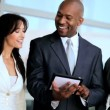 Multi Ethnic Business Team Using Wireless Tablet - Stock Photo