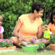 African American Girls & Their Mother Gardening Together — Stock Video #23247824