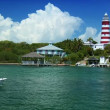 Stock Video: Tropical Island Lighthouse with Passing Craft