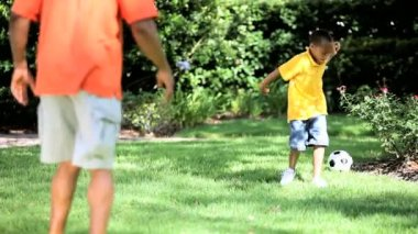 Ethnic Father & Son Kicking a Ball Together — Stock Video